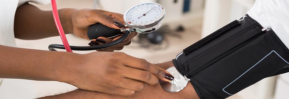 A physician measures a patient's blood pressure.
