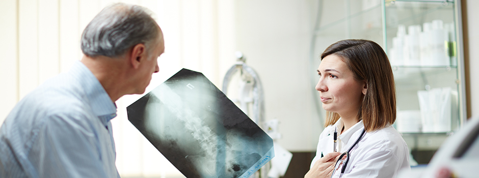 A patient and orthopedic surgeon discussing a scan.