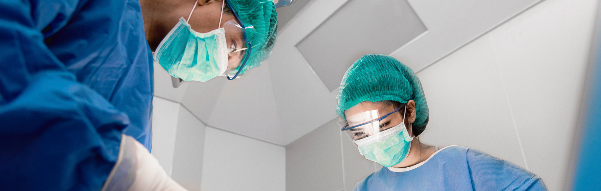 Close-up of surgeons wearing masks while performing a procedure in an operating room
