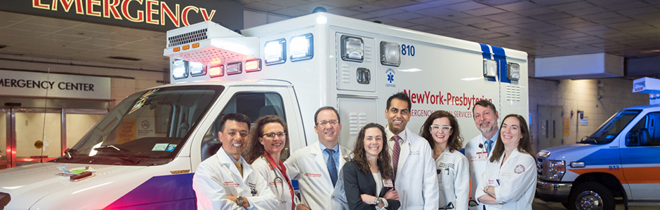 Group photo of Emergency Medicine physicians in front of an ambulance.