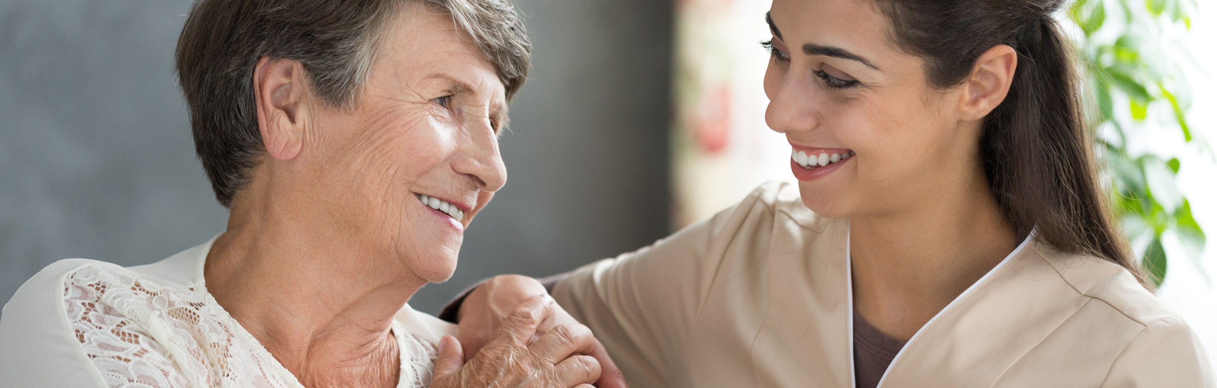 Nurse interacts with an older patient.