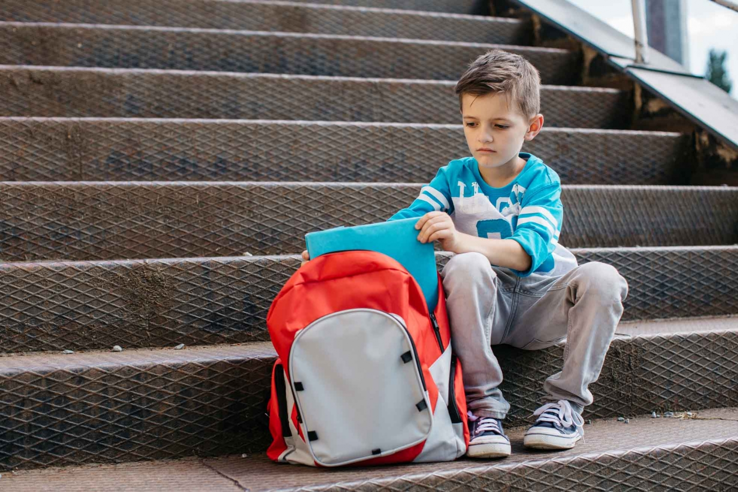 Sad young boy sitting on steps with backpack