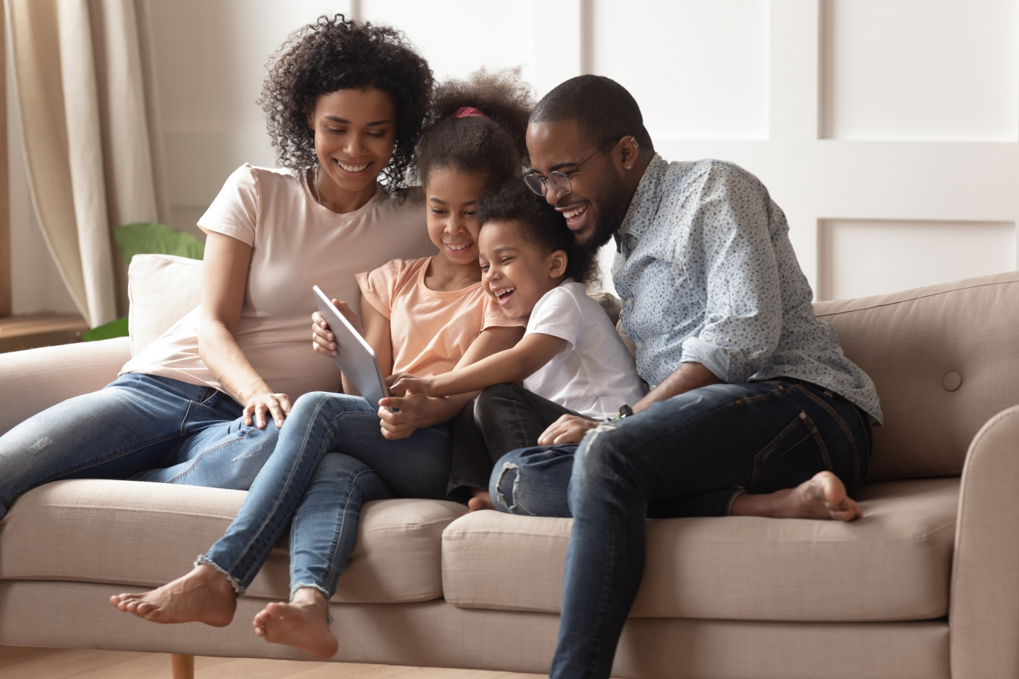 A family sits on a couch and gathers around a tablet