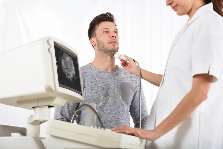 Man receiving an ultrasound of his thyroid