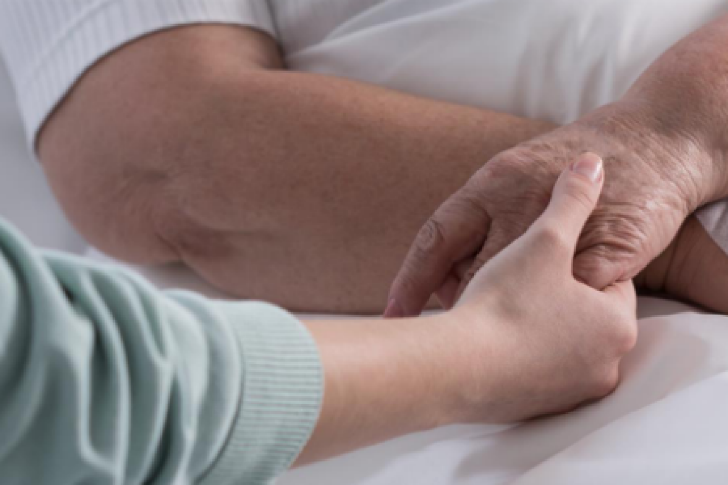 Someone holds a patient's hand