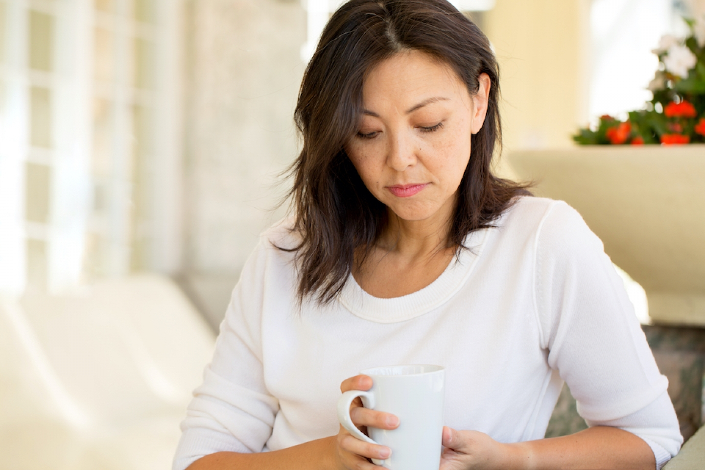 woman looks down at cup