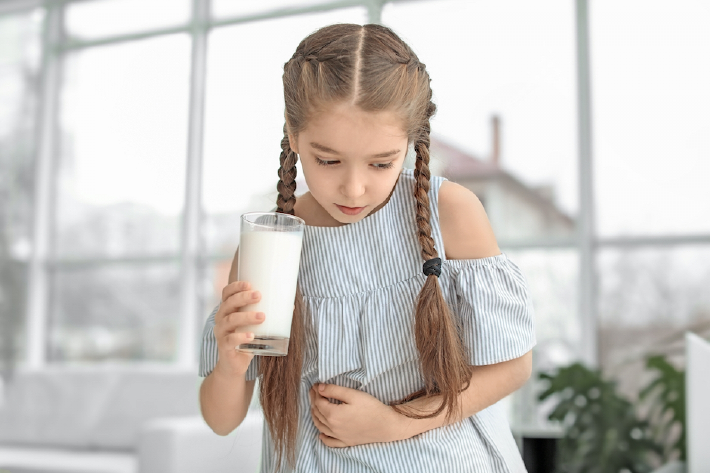 child with milk in her hand