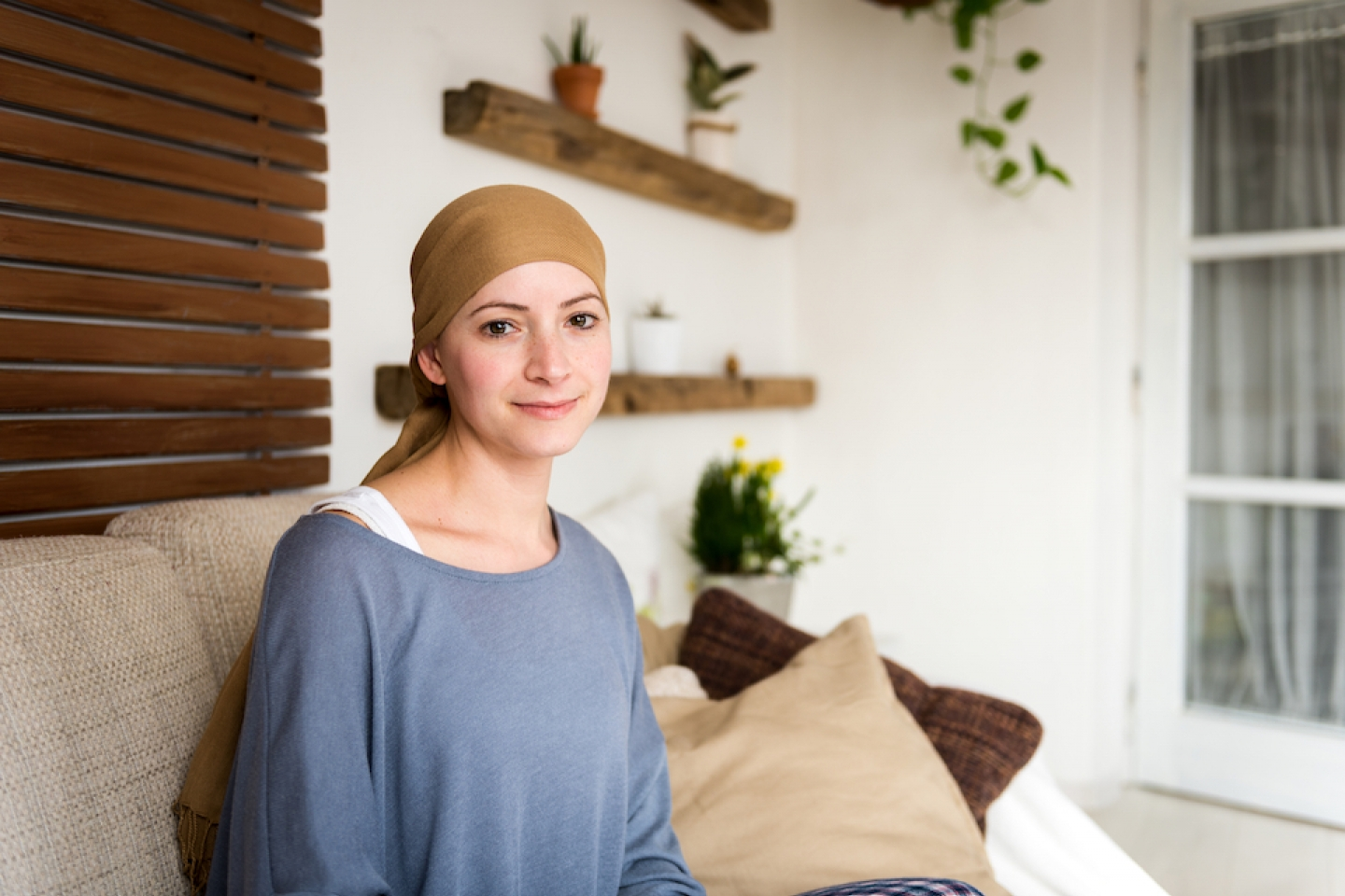 young positive adult female cancer patient sitting in living room