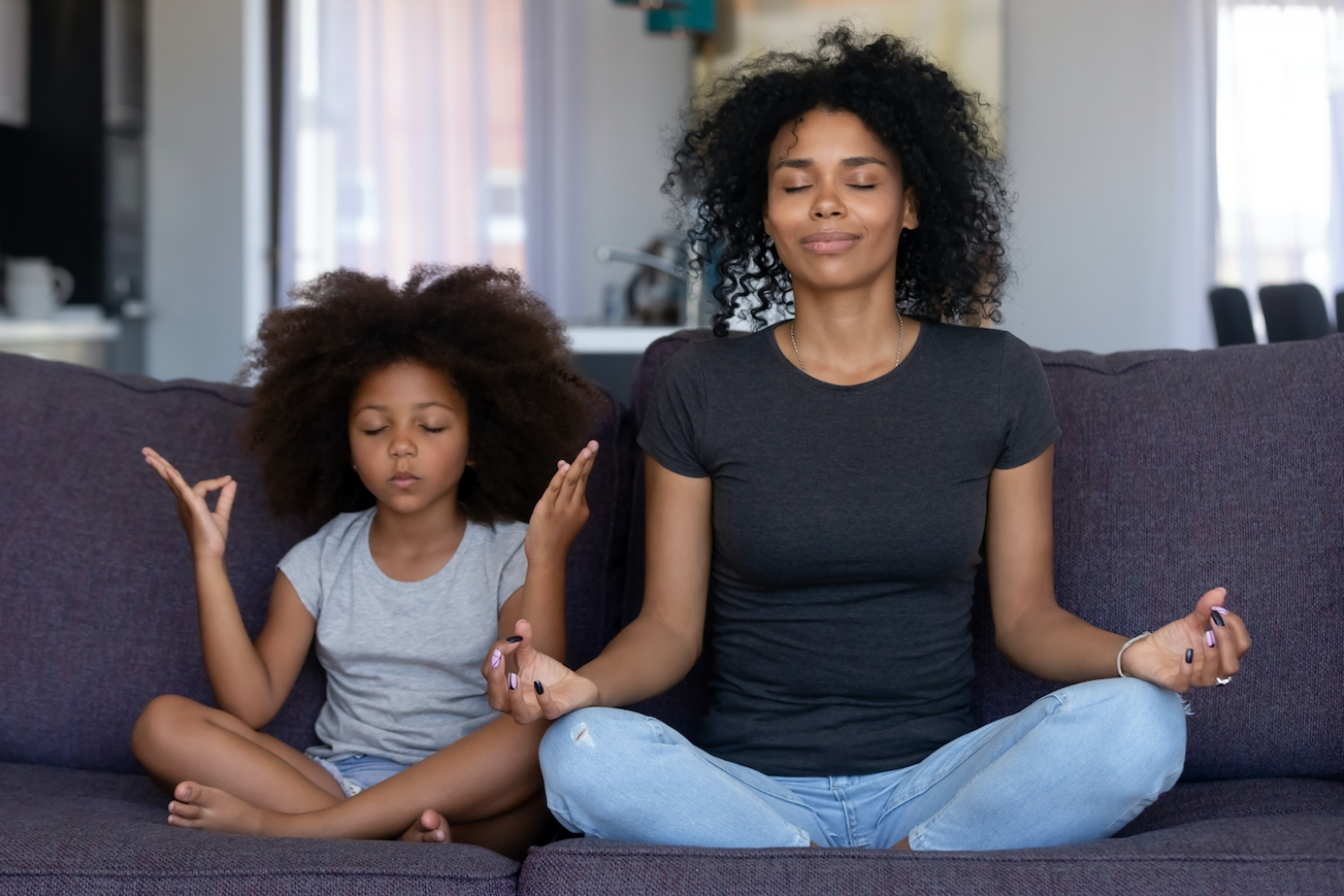 mom and daughter meditating on couch