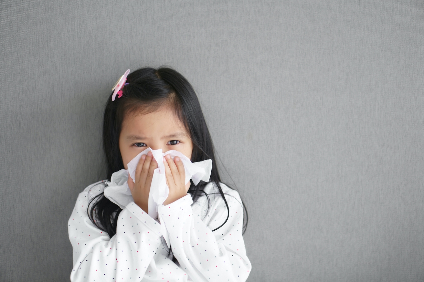 young girl sneezing into a tissue