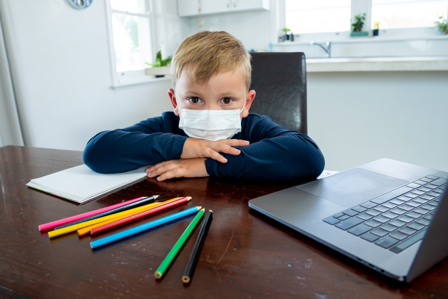 child with face mask on at desk with laptop, paper and coloring pencils