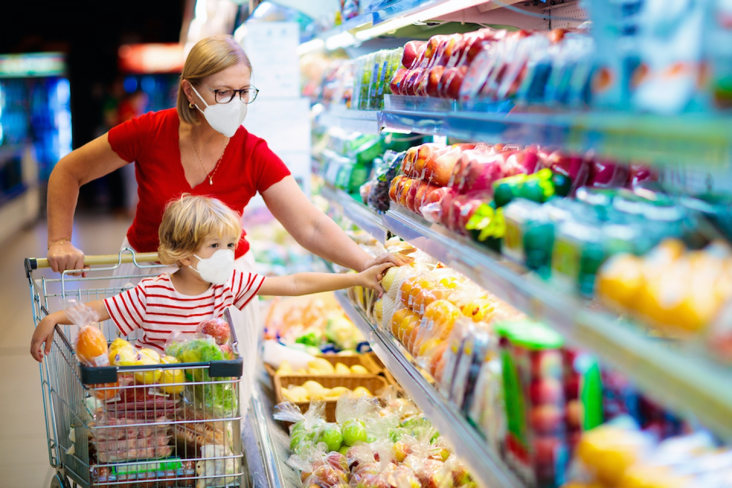 mom and son wearing masks and picking food at the grocery store