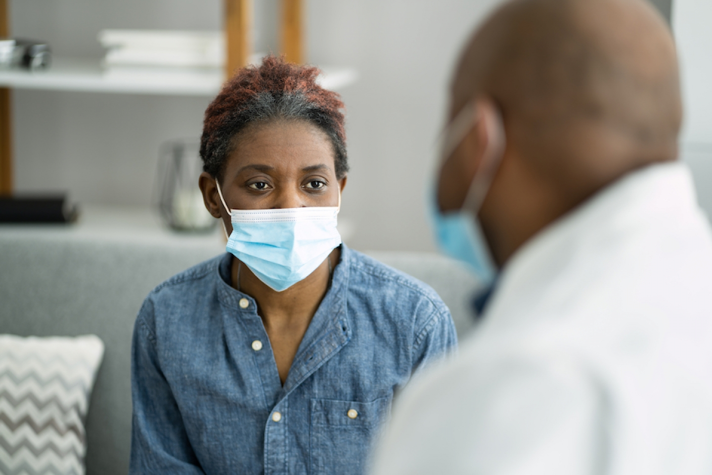 black women patient with face mask on meeting with her doctor