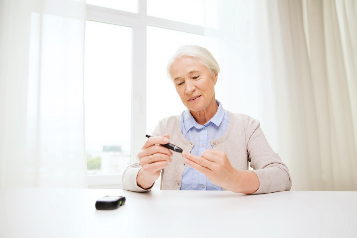older woman checking blood glucose levels