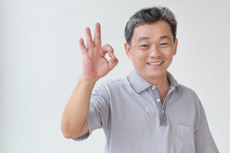 older asian man holds hand sign