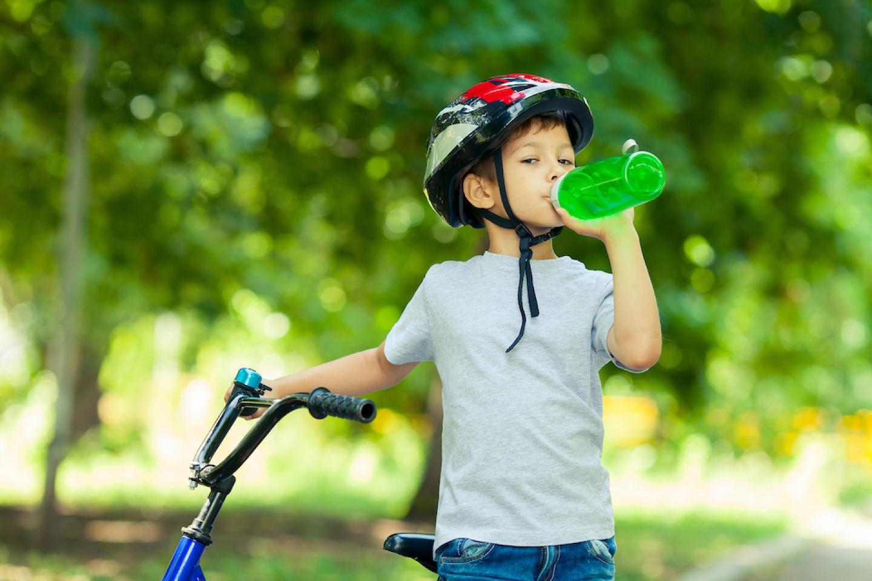 child on bike drinking water