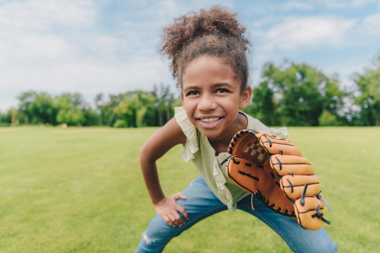 young girl wearing a baseball glove