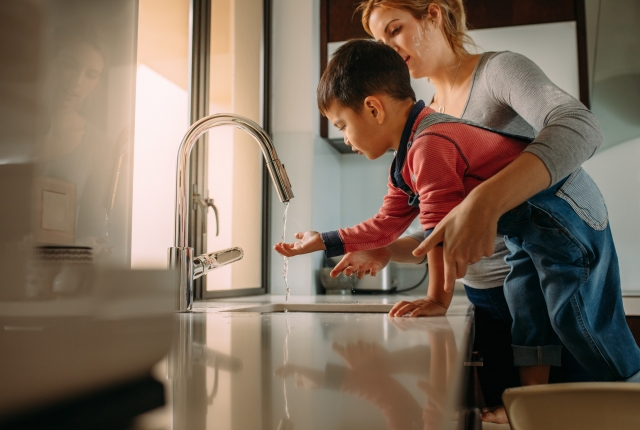 Mother helping son wash his hands at a sink