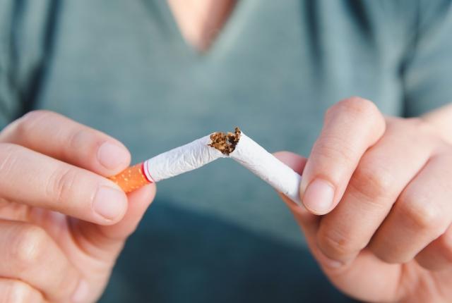 Person breaking a cigarette in half.