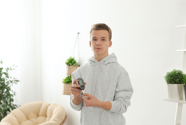 Teen boy holding digital glucometer at home