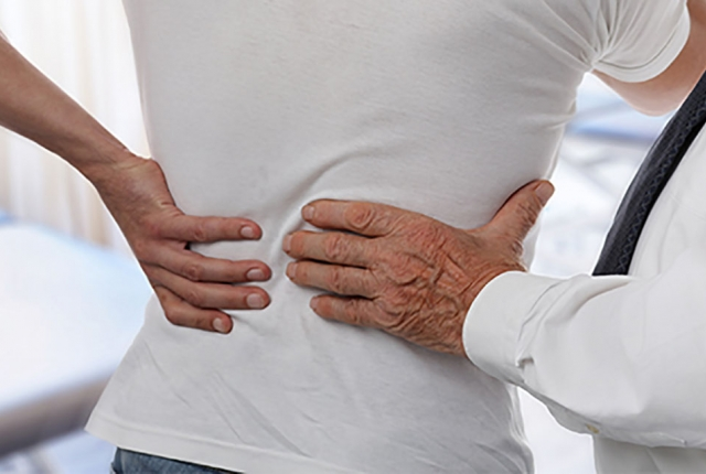 Physician examines patient with back pain.