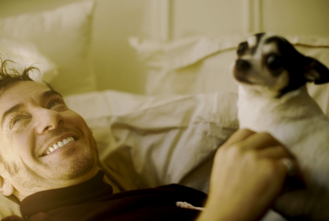 Feature patient Timothy is smiling with his dog sitting on his lap