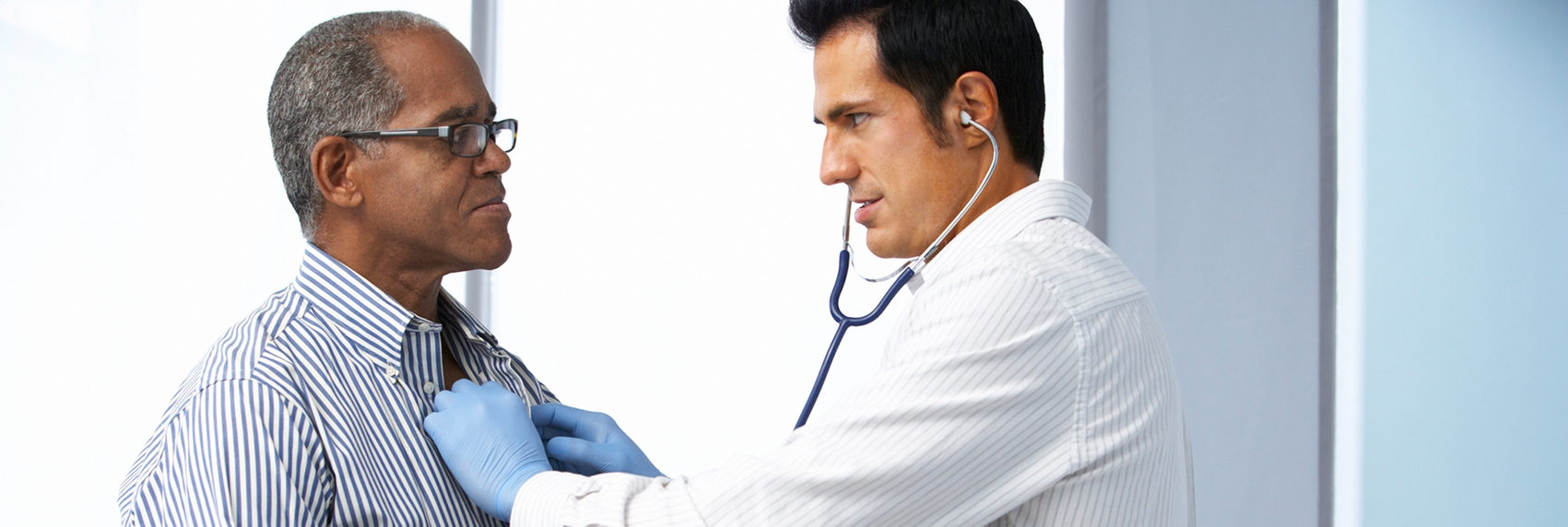 Male doctor listening to older patient's heart using a stethoscope.