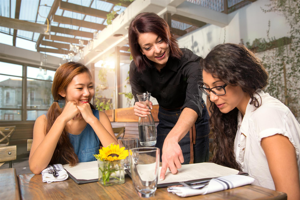 Women interacting with waitress at restaurant.