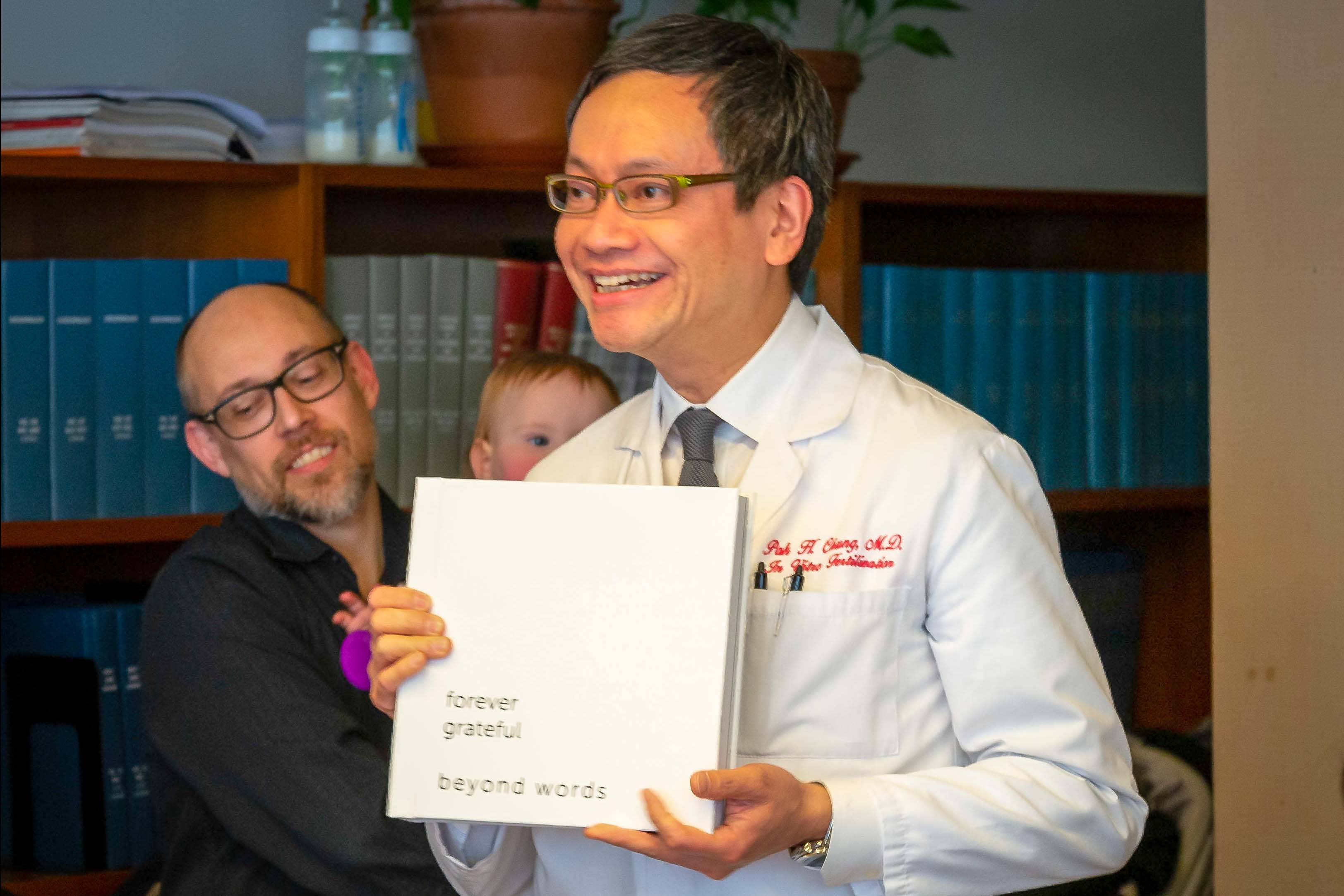 Dr. Pak H. Chung poses with an album gifted by patients.