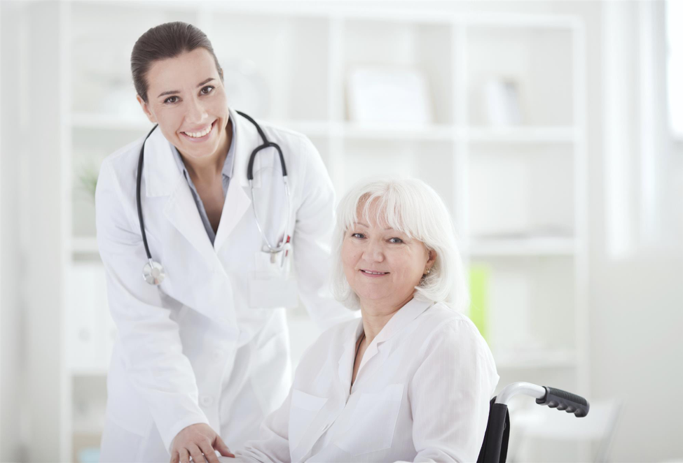 Female doctor stands with elderly female patient