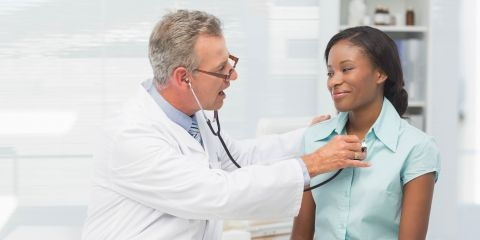 Doctor checking patient's heartbeat.