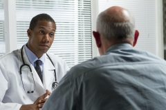 black male doctor meets with older male patient