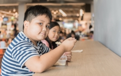 obese child eating at food court