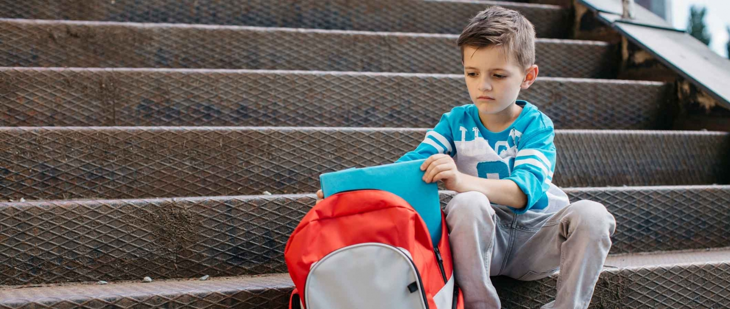 Young boy sitting on stairs with a backpack